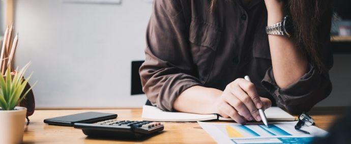 Une gestionnaire de paie en train d'analyser et traiter diverses informations avant de les intégrer à un logiciel de paie.
